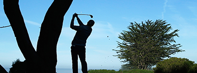Silhouette of player hitting a golf shot